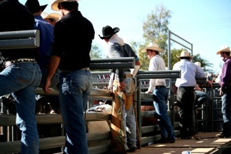 Bull riders stand behind the shoots and prepare themselves for their next ride. Others help the upcoming bull rider on his bull and keep him safe. (Naomi Klocmann/Borderzine.com)