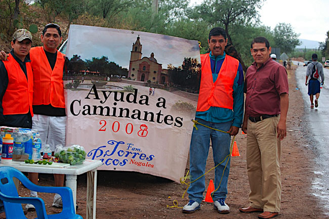 Members of the Torres Picos family offer their support to walkers with water, lemons, and medicines. (George Thomson/Borderzine.com)