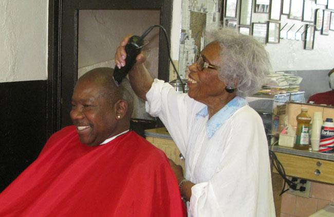 Barber Estine Davis taking care of Dr. Donald Phifer a customer of her for 25 years. (Eddie Delgado/Borderzine.com)