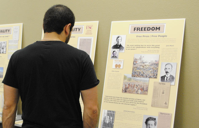 A student reads a poster dedicated to Padre Félix Varela and writer José Martí who published newspapers in the U.S. to support freedom in their countries of origin. (Lourdes Cueva Chacón/Borderzien.com)