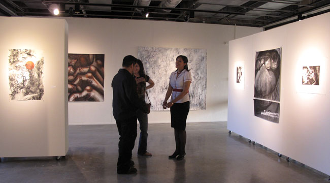 Artist Yvianna Hernandez (right) at UTEP's Glass Gallery surrounded by her drawings and paintings. (Lucía Murguía/Borderzine.com)