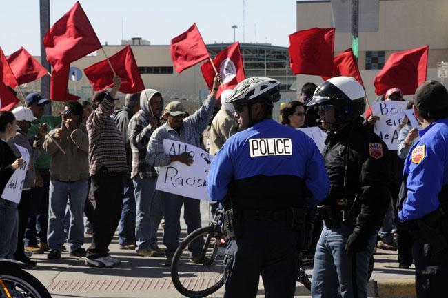 Manifestantes de la Asociación de Trabajadores Fronterizos enarbolan banderas rojas a la vez que reclaman justicia. (Jorge Jiménez, cortesía de El Diario de El Paso)
