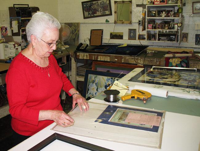 Ana Cortez getting ready to frame a customer's invaluable memories. (Justin Monarez/Borderzine.com)