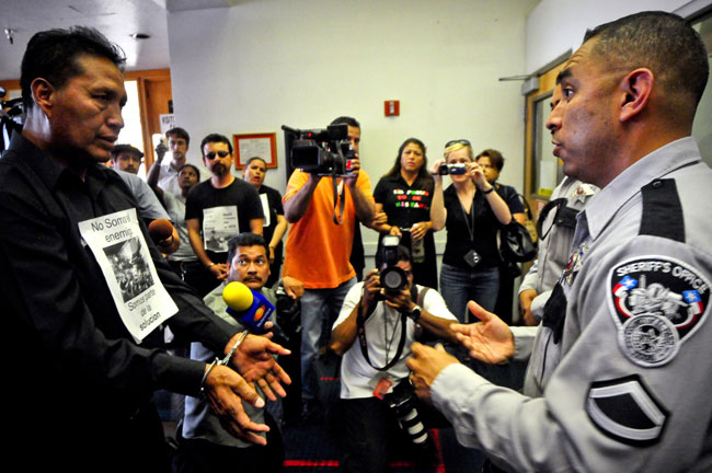 El oficial Jesse Tovar, vocero de la Oficina del Sheriff, recibe a manifestantes. (Víctor Ramírez/Borderzine)