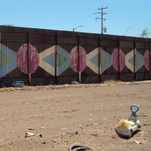A child's discarded push car toy lies among the empty bottles, televisions, tires and other debris in front of the two-mile mural painted on the international border fence separating  Calexico and Mexicali.  There are no plans to repaint the mural as it begins to fade.  --Photo by Stacy Garcia