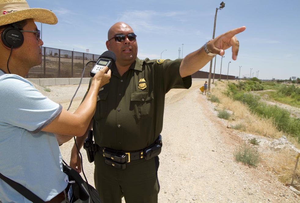 Border Patrol officer, Ralph Gomez, talks to reporter Seok Kang at the international border. (Christopher Karadjov/Borderzine.com)