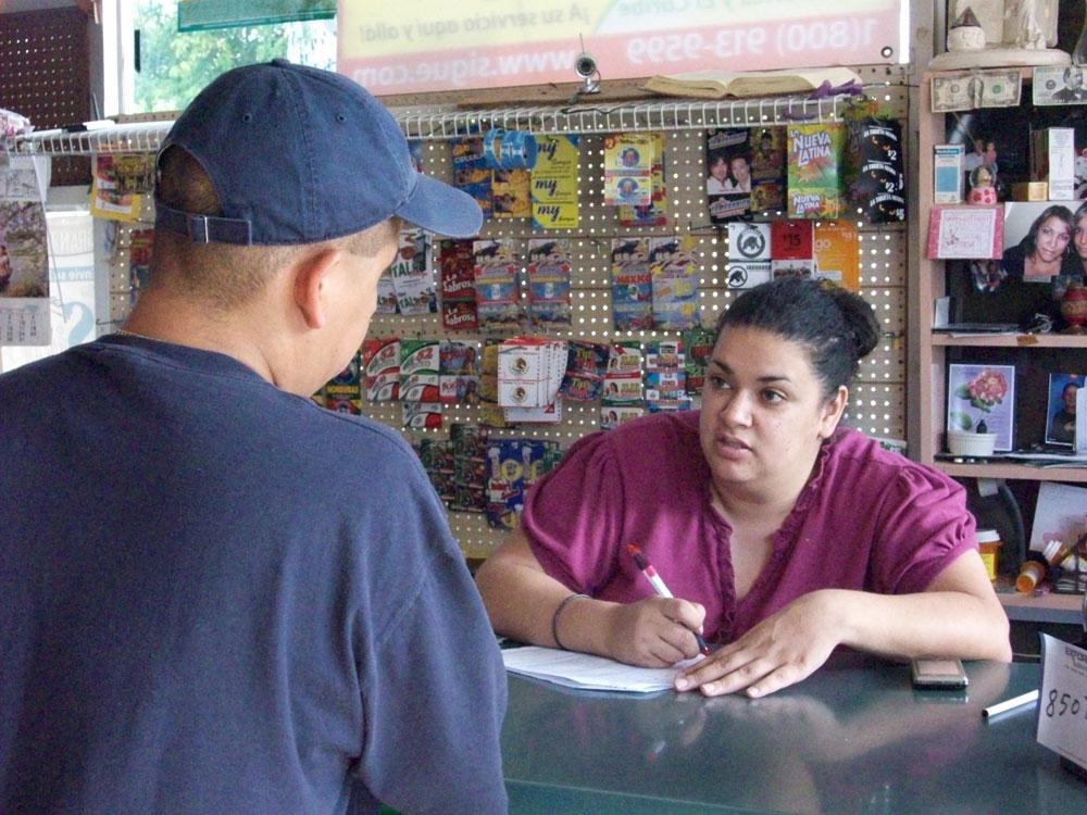 Michelle Cigarroa se prepara para transferir dinero de Ángel Alonzo en la tienda La Mexicana. El hecho de que Alonzo manda menos dinero hoy en día ha afectado a su familia en la Cuidad de México. (Jessica Harbin/Cortesía de etsujournalist.com)