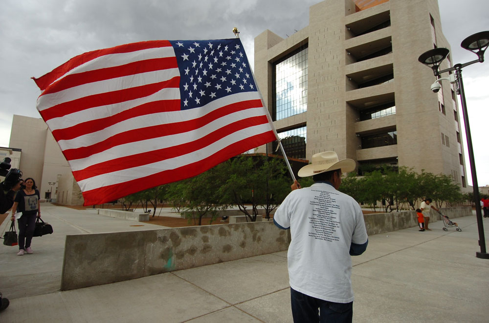 Un manifestante porta una bandera de los Estados Unidos frente a la Corte Federal. (Juan Torres/Borderzine.com)