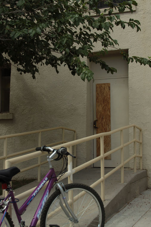 Puerta de ingreso a Bell Hall. La placa vertical de madera reemplaza al vidrio que fuera impactado por la bala antes de incrustarse en la oficina 111. (Raymundo Aguirre/Borderzine.com)
