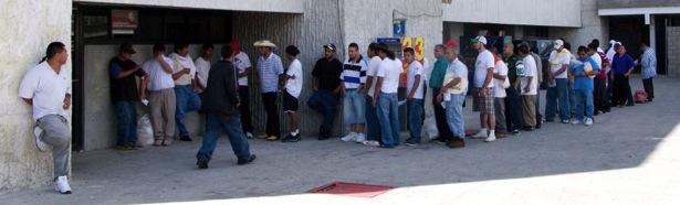 Deportees in line to make a free phone call at the office of Coordinación de Atención a Migrantes, Juárez. (David Smith-Soto/Borderzine.com)