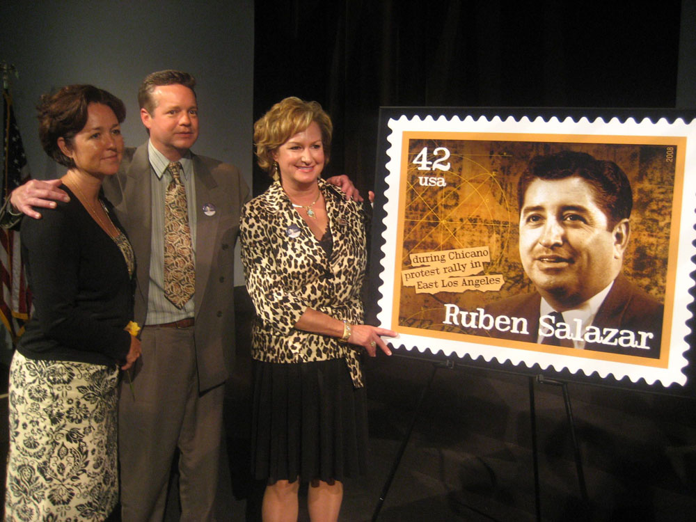 Stephanie Salazar Cook (left), John Salazar and Lisa Salazar Johnson with replica of the stamp that honors their father.