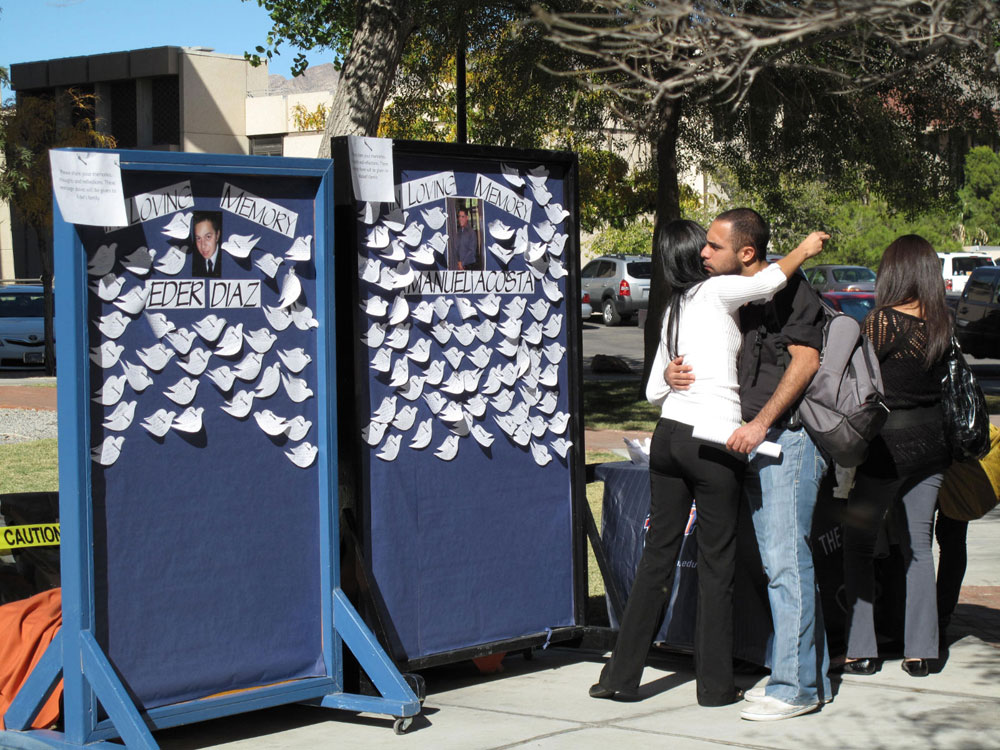 White paper doves, with written messages from their friends, surrounded the pictures of Acosta and Diaz. (Danya Hernandez/Borderzine.com)