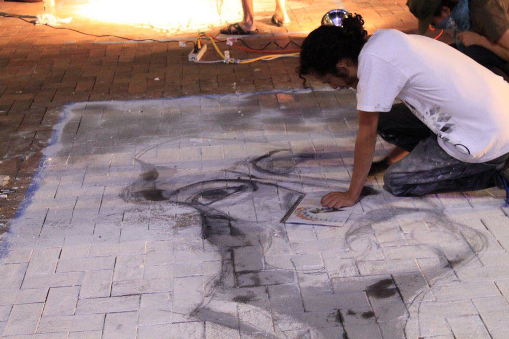 "Artist ""Werk"" studies his sample piece before adding detail to final product. (Marko Morales/Borderzine.com)"