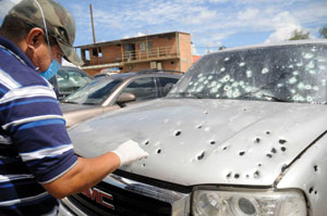 A police investigator looks for evidence following a drug-related hit in Hermosillo, Mexico. (Courtesy of Knight Foundation)