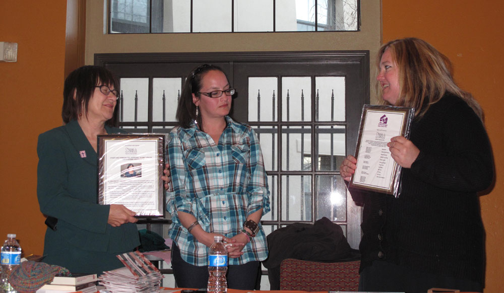 Dr. Moira Murphy (right) hands plaques to Professor Dr. Kathy Staudt (left) and Irma Casas from Casa Amiga to show appreciation to the non-profit organization.