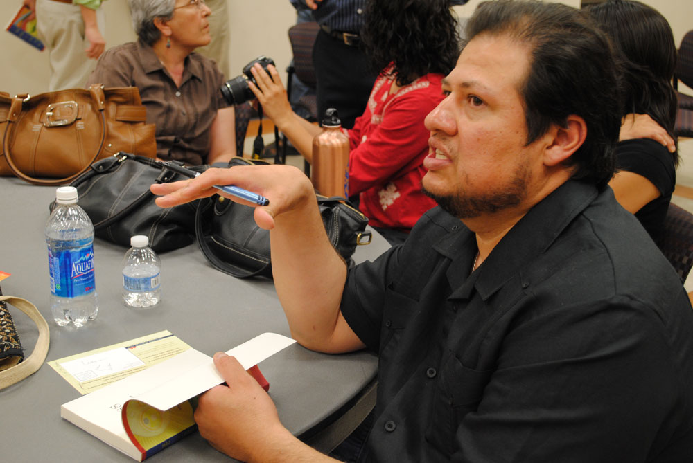 "Richard Yanez, author of the novel ""Cross Over Water"" autographs a copy of his book during a signing at the UTEP campus Friday, April 22, 2011. (Miguel J. Cervantes/Borderzine.com)"