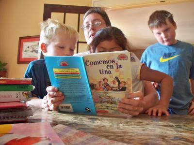 Karen Childress (center) teaches Foster and Susana to read in Spanish. (Collin Brooks/El Nuevo Tennessean)