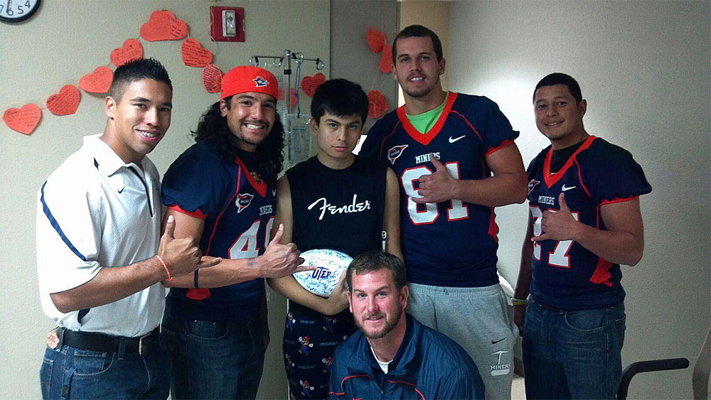 UTEP football team members visit Bobby (center) to give him a signed football while in the hospital. (Courtesy of Bobby Garcia)