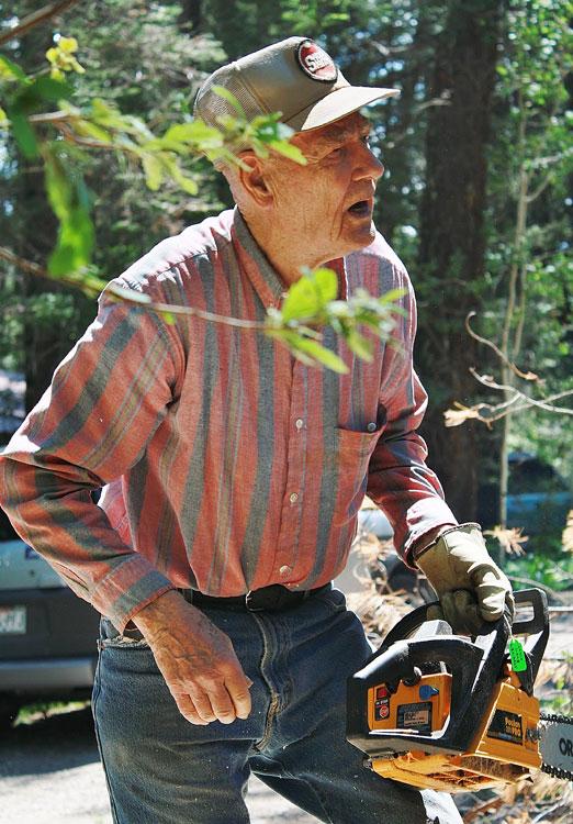 Louie Long, of Cloudcroft,  WORKING on cutting down a dead tree. (Cheryl Howard/Borderzine.com)