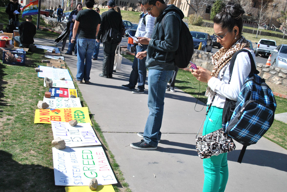 Protest signs and books call students' attention at Leech Grove on the UTEP campus. (Lourdes Marie Ortiz/Borderzine.com)