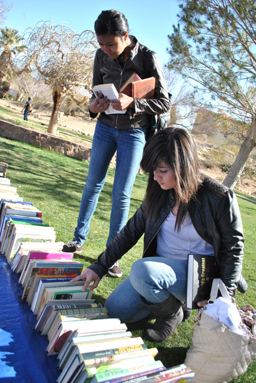 Neyma Gonzalez (standing up), freshman engineering major, and Andrea Caraveo, freshman forensic science major, look at books to buy at the Occupy El Paso book sale. (Lourdes Marie Ortiz/Borderzine.com)