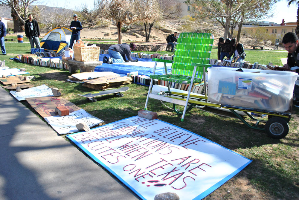 Members of Occupy El Paso help by making poster signs and setting up a tent that has become the symbol of the Occupy movement. (Lourdes Marie Ortiz/Borderzine.com)