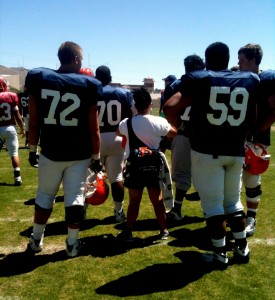 Female UTEP athletic trainer standing between towering football players.