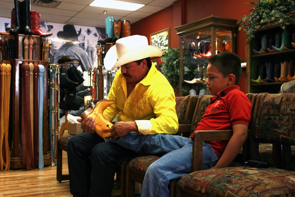 Ricardo Arellano helps out his 8 year-old son trying new boots at Juarez Boots. (Adolfo Mora/Borderzine.com)