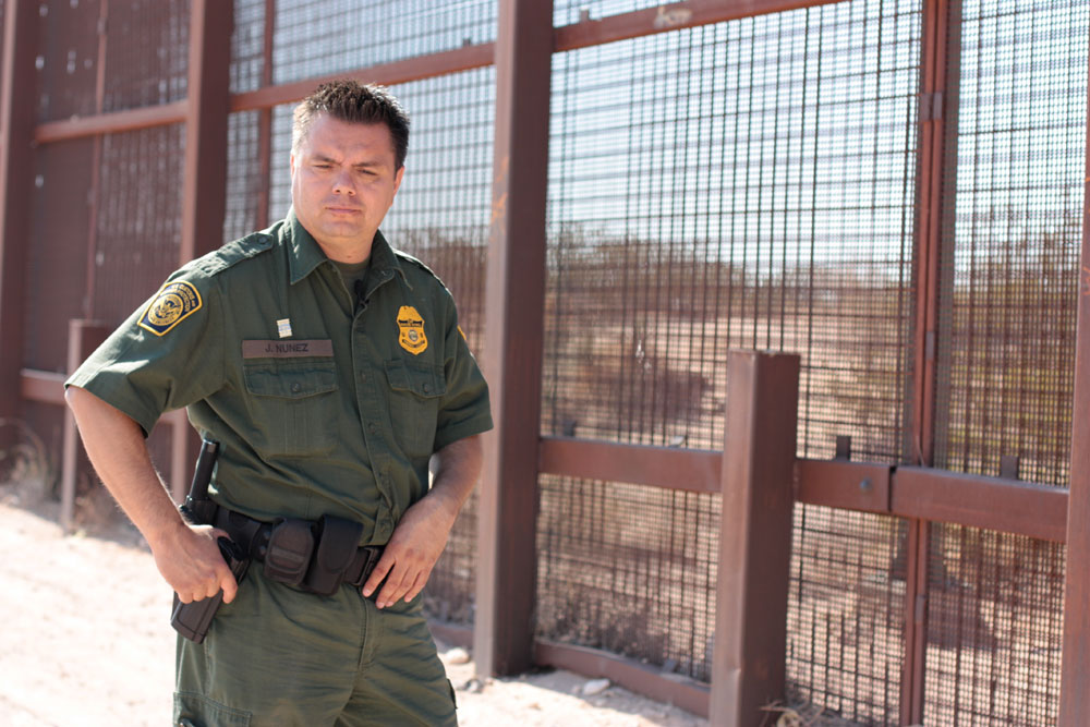 Border Patrol Agent, Jacob Nuñez, walks along a standard pedestrian fence in New Mexico. The fence is an example of a collaboration between the Border Patrol and local landowners. (Mariana Dell/Borderzine.com)