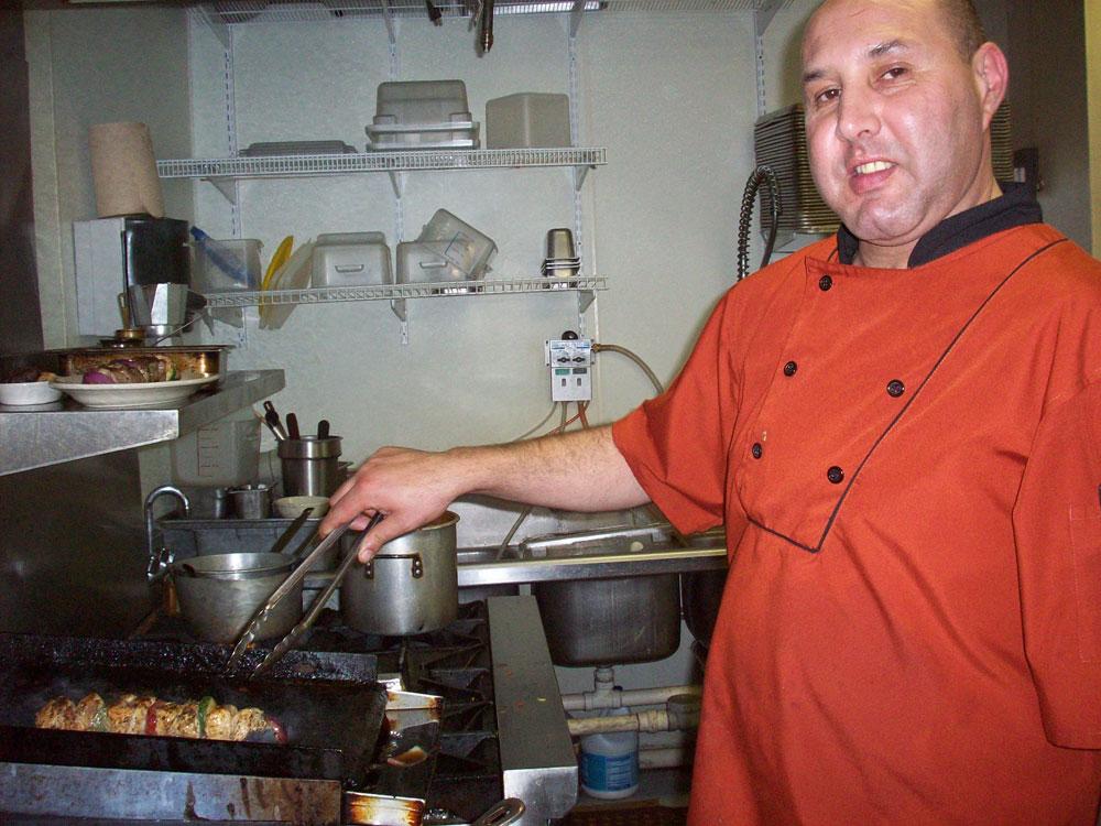 Zino Souikni cooking shish kebab. (Anoushka Valodya/Borderzine.com)