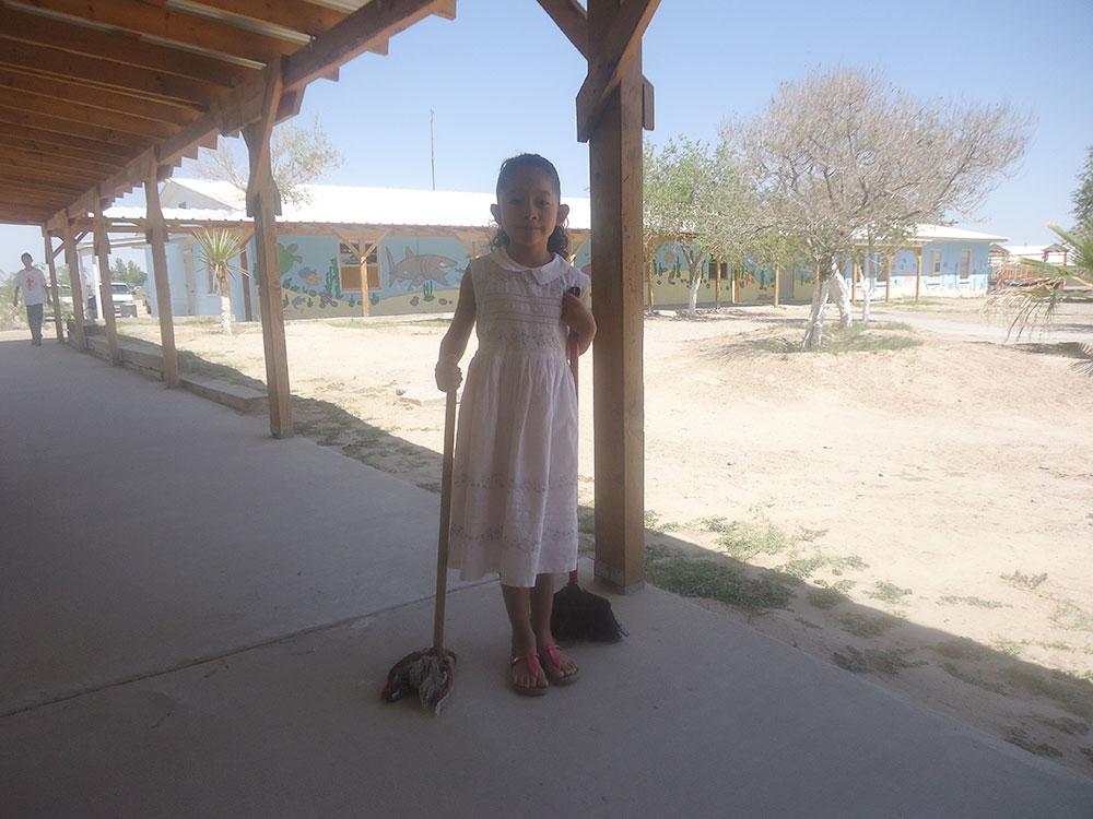 Esmeralda works on her chores before play time. (Diana Arrieta/Borderzine.com)