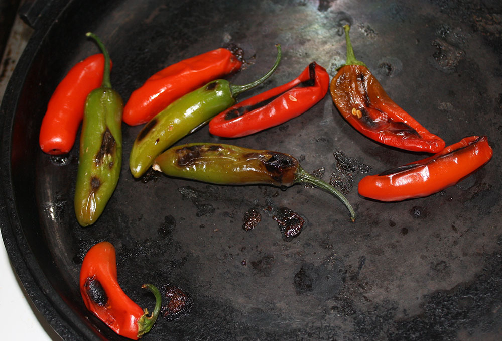 Roasting serranos for the salsa on a comal. (Cheryl Howard/Borderzine.com)