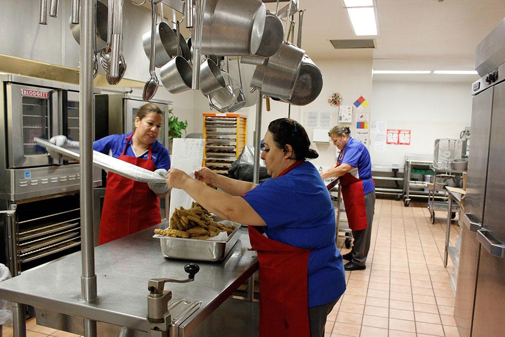 Helper Natividad Vasquez (right) and cook Lupita Ceron de Navarrete prepare steak fingers at Hillcrest Middle School. (Brenda Armendariz/Borderzine.com)