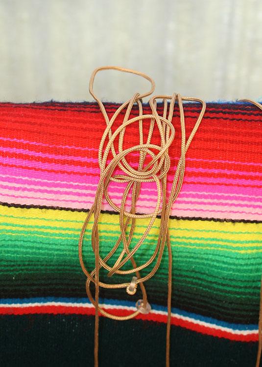 Bamboo roll-up shade tying itself in a knot. (Cheryl Howard/Borderzine.com)