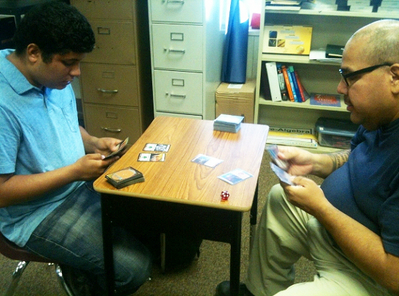 "Jovan Rojas, 18, left, plays a card game against video game club tutor John Olivo, 43, on Monday Dec. 3, 2012. The game being played is ""Magic: The Gathering,"" a card game that pits players against monsters and wizards and teaches mathematical skills. -- Photo by Kevin Iqueda"