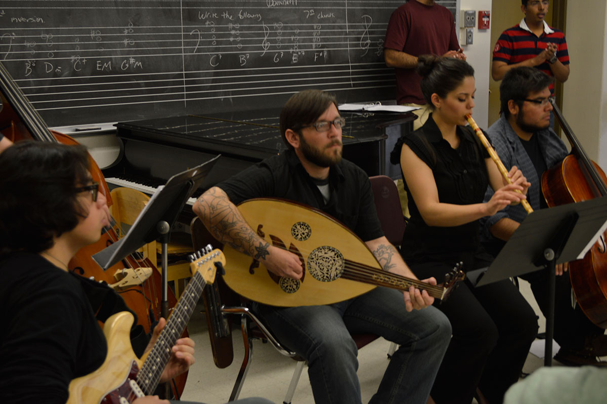 Senior Jecoa Ross plays the oud along with other students during Layali Al-Sham's rehearsal. (Paul Reynoso/Borderzine.com)