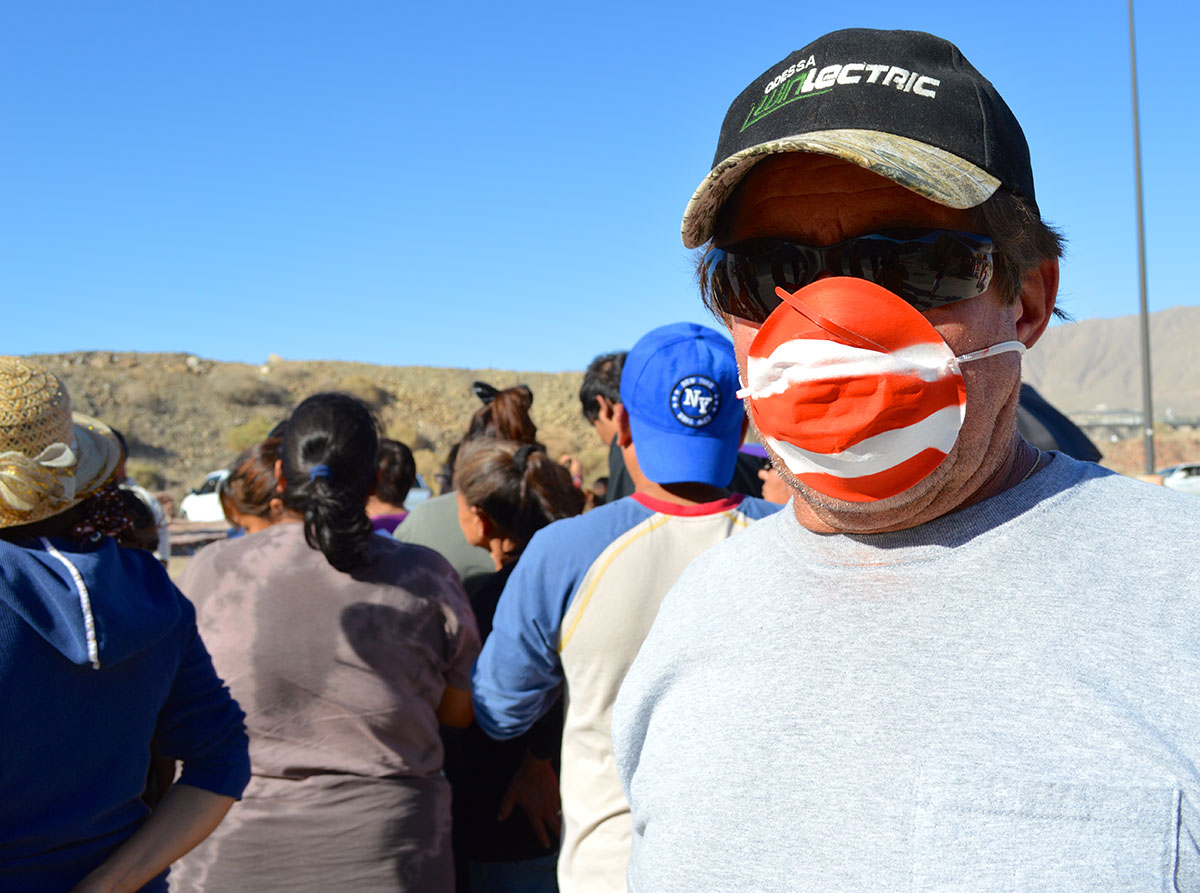 Lorenzo Najera wears a red and white mask as he protests. (Sarah A. Duenas/Borderzine.com)