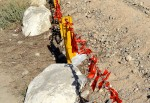 Red ribbons line a small metal fence that surrounds the International Boundary Marker #1. (Sarah A. Duenas/Borderzine.com)