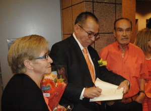Veteran journalist Alfredo Corchado accompanied by his parents signs copies of his book Midnight in Mexico. (Gustavo Aguirre/Borderzine.com)