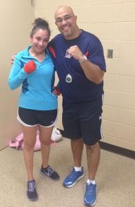 Boxer Amanda Ramirez poses next to his trainer, Herman Delgado. (Frankie Rodriguez/Borderzine.com)