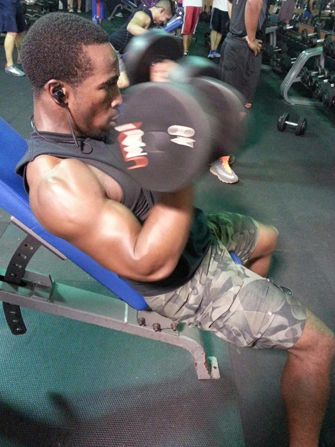 """""""Curling 40 pounds to work biceps"""". (Cristina Quinones/Borderzine.com)"""