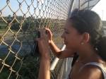 Lupita takes a picture of the Rio Grande River. (Sergio Chapa/Borderzine.com)