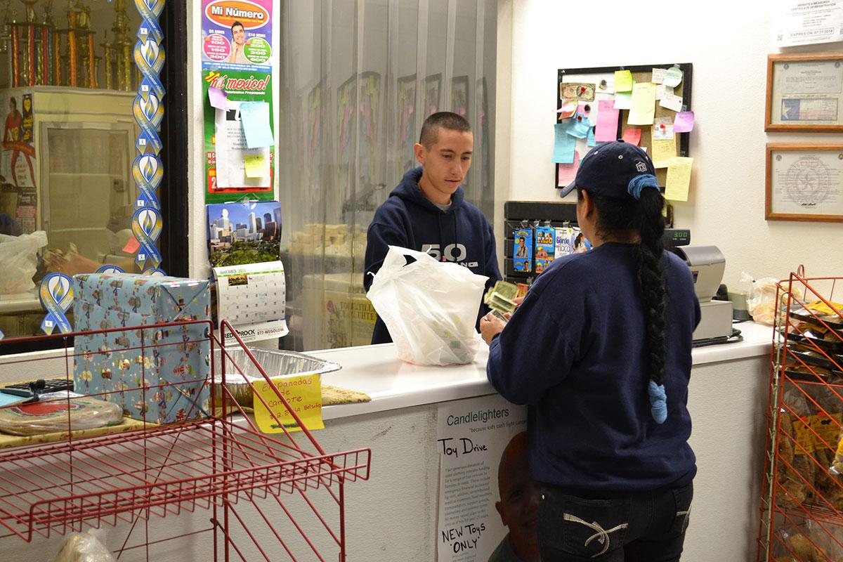 Omar Montiel, 2, atendiendo a un cliente. La tortillería produce más de 2,000 libras de tortillas al día. (Estefany Galindo/Borderzine.com)