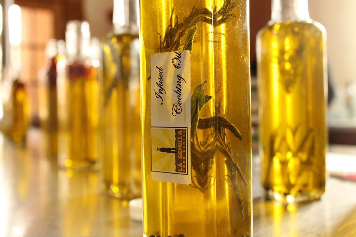 The results of a workshop at La Semilla on how to produce herb infused cooking oil. (April Lopez/Borderzine.com)