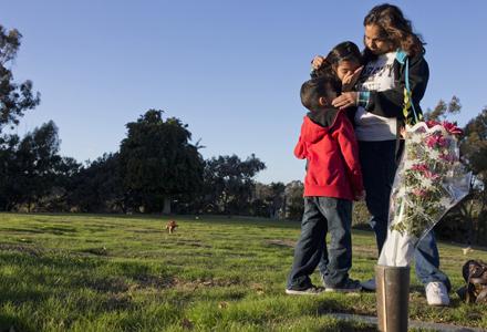 Annabell Gomez visits the burial site of her daughter, Valeria Tachiquin-Alvardo, on Dec. 4, 2013, with two of her grandchildren Analya Alvarado, 11, and Israel Alvarado, 6. (Nick Oza /The Republic)