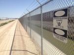 A canal and the border fence at the Ysleta International Bridge. (Sergio Chapa/Borderzine.com)