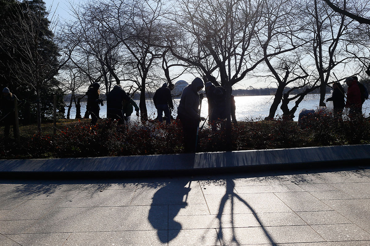 Ana McBayna and other Impact volunteers pick up debris off the Tidal Basin. (Aaron Montes/HispanicLink)