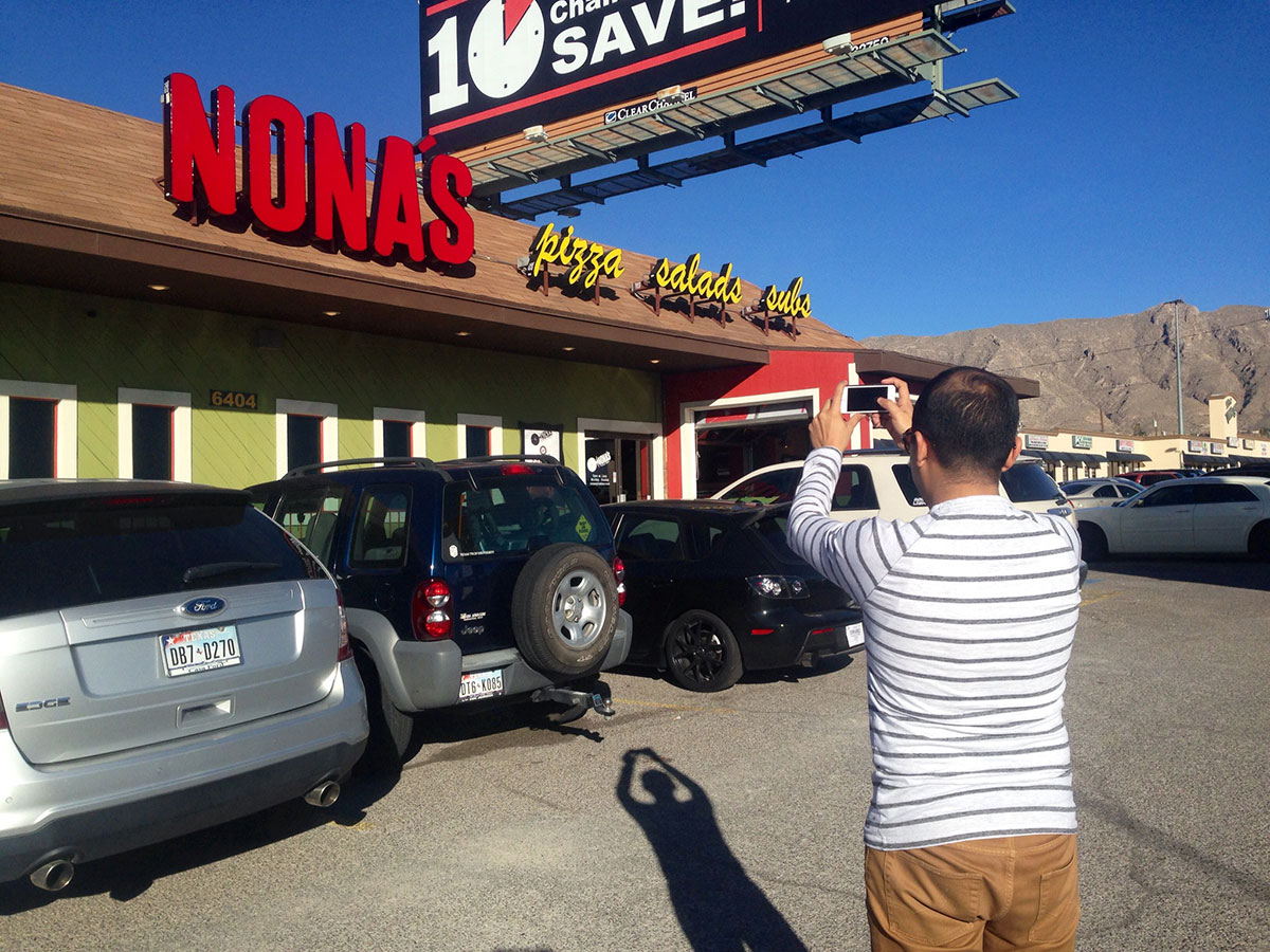 Junior Vasquez takes a picture in front of local restaurant, Nona's Pizza Bar, for an Instagram post. (Yvette Kurash/Borderzine.com)