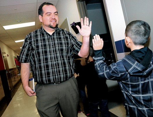 Columbus Elementary School Principal Armando Chavez high-fives students in the school hallway as they change classes. (Robin Zielinski - Sun-News)