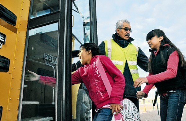 Former port director Joseph Rivera, now a substitute teacher for the Deming school district, assists students Iris Carbajal, 11, left, and Viviana Ramirez, 11, onto the school bus after they crossed the U.S.-Mexico border. (Robin Zielinski - Sun-News)